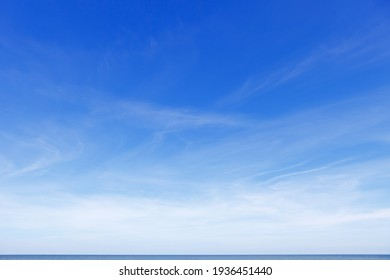 Beautiful blue sky over the sea with translucent, white, Cirrus clouds. The horizon line