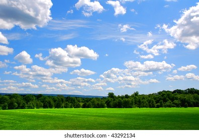 Beautiful blue sky with puffy white clouds over a grassy field in the mountains