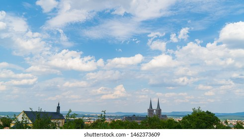 Beautiful blue summer sky with bright clouds and a old medieval town in a rural landscape