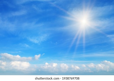 Beautiful, blue summer sky with fluffy clouds and bright sun as a background