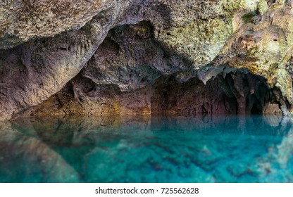 Beautiful blue underground waters contrasting with orange rock formations, The Three Eyes National Park, Dominican Republic.