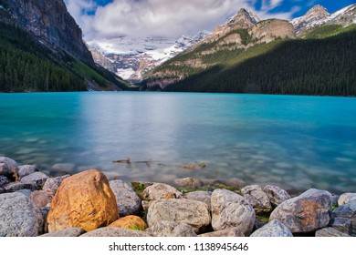 The beautiful blue water. Lake Louise this best. Rocks in the foreground and the surrounding mountains forms a great canvas.