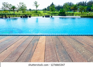 Beautiful blue water ,swimming pool for background and empty wood floor .Blank space for text and images.