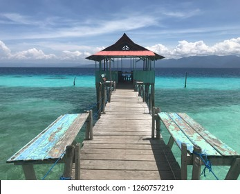 Beautiful blue watercolor beach with a long wooden bridge and floating house in Ambon Indonesia