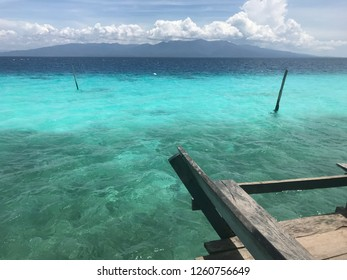 Beautiful blue watercolor beach with mountain background in Ambon Indonesia