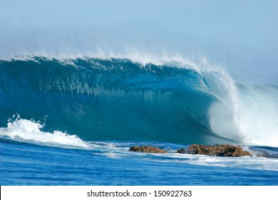 A beautiful blue wave crashes into the rocks at Inhaca Island, Mozambique.