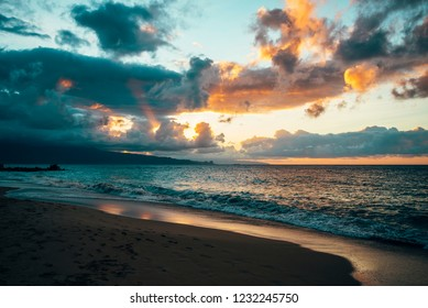 Beautiful Blue Wave Crashing on Sandy Seashore with Colorful Sunset Sky and Sun Rays Coming Through Clouds in Scenic Background a in Tranquil Tropical Island Paradise Nature Scene of Maui Hawaii
