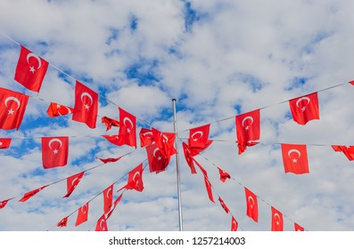 Beautiful blue and white sky with many red turkish flags hanging. Horizontal color photography.