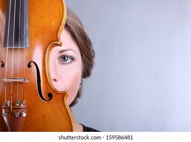 beautiful blue-eyed girl in a dark blue evening dress holding a violin handmade portrait on gray background