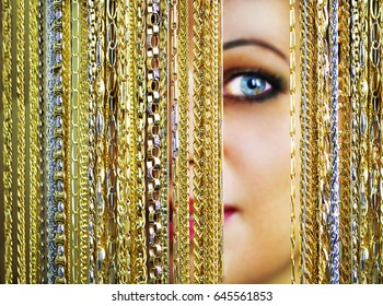 Beautiful blue-eyed woman looks through the gold chains Look into our shop! - Jewelery shop advertisement concept