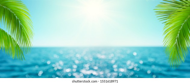 Beautiful Blur defocused blue sea background with palm leaves. Landscape of tropical summer. Summer vacation concept