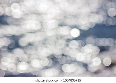 Beautiful blurred blue and white abstract water background with bokeh. Defocused sea surface water in the sunshine with sun flare.