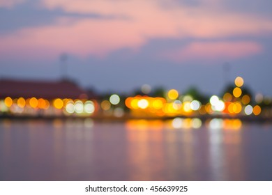 Beautiful blurred city lights with bokeh effect reflected on water background