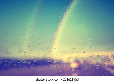 Beautiful blurred vintage photo of raindrop on windshield on motion blurred highway road with two rainbows in background.