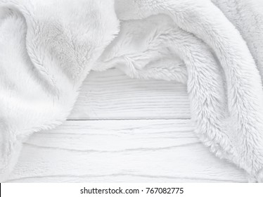 Beautiful blurred white fur on a worn wooden background as a New Year, Christmas or winter background (with copy space in the center), selective focus
