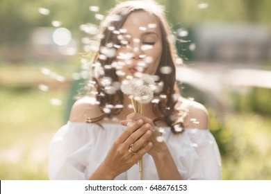 Beautiful blurry girl blowing at the dandelion at camera. Simmer time pretty woman outdoors with blowball