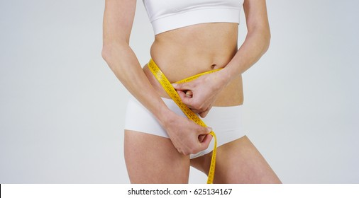 Beautiful body of a young girl measuring a waist,belly ruler,on the white background. Concept:diet,proper nutrition,sports body,slender body,work on yourself,love yourself,achieve,caring for the body.