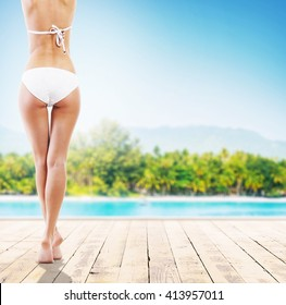 Beautiful body of young and sexy woman. Sea, sky, palms and beach background. Summer vocation concept.