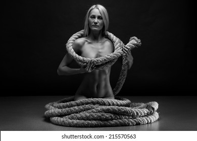 Beautiful body of young woman with a rope over dark background