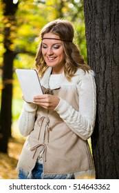 Beautiful boho girl enjoys using digital tablet in the park.Boho girl using digital tablet