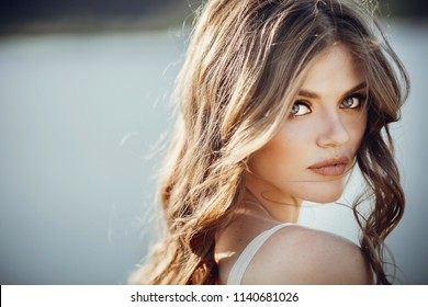 beautiful boho girl portrait with amazing eyes and lips standing near lake. attractive young woman in white bohemian dress with windy hair posing on sand beach near water