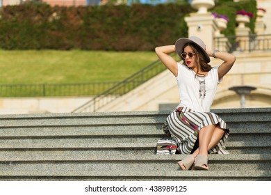 Beautiful boho girl sitting on the stairs