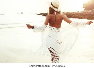 Beautiful boho styled model wearing white crochet swimsuit posing on the beach in sunlight