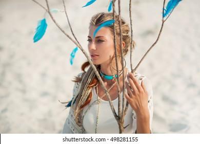 beautiful boho woman sitting on sand outdoors