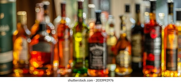 Beautiful bokeh from a row of alcoholic bottles in backlight. Panoramic shot.