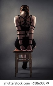 beautiful bondage woman sitting with back on chair