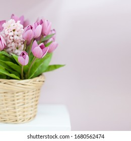 Beautiful bouquet of artificial tulips and hyacinth in a wicker basket.