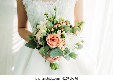 Beautiful bouquet. The bride is holding a bouquet in her hands. Flowers of the bride. The bride is waiting for the groom in the white room.
