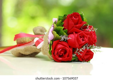beautiful bouquet of bright red flowers, on  table on green background