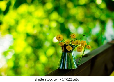 Beautiful bouquet of buttercups or daisy in small tin jar on sunny bokeh green and yellow background, Summer house concept. Selective focus.