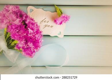 Beautiful bouquet of carnations on a blue board.