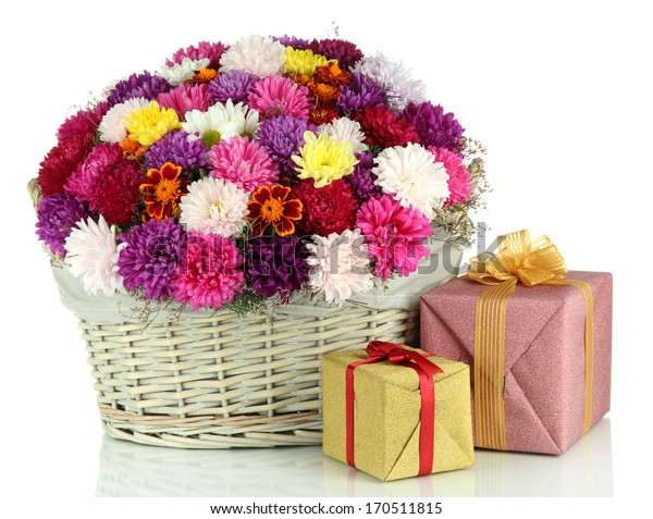 Beautiful bouquet of chrysanthemums in wicker basket isolated on white