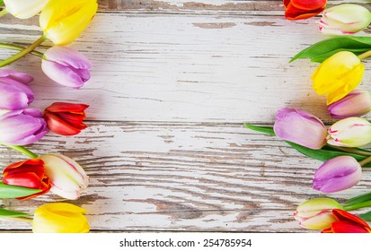 Beautiful bouquet of colorful tulips flowers on wooden table, close-up.