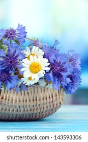 Beautiful bouquet of cornflowers and chamomiles in basket on blue background