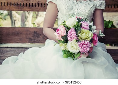 beautiful bouquet of different colors in the hands of the bride in a white dress sitting on wooden bench