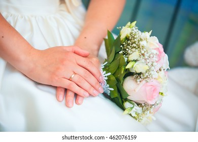 beautiful bouquet of different colors in the hands of the bride in a white dress.
