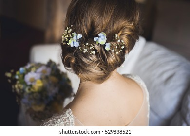 beautiful bouquet of different colors in the hands of the bride in a white dress from the back hair hairstyle blue flowers
