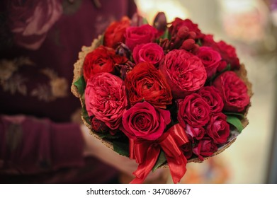 beautiful bouquet of different  red flowers in hands