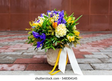 Beautiful bouquet of flowers: iris, mimosa, tulip, matricaria, rose, lisianthus