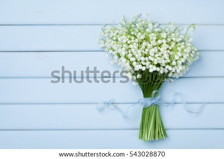 Beautiful bouquet of flowers lily of the valley on  blue wooden table from above.