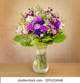 a beautiful bouquet of flowers, multi-colored roses with green leaves stands in a glass vase with water on a light brown table