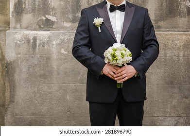 Beautiful bouquet of flowers ready for the big wedding ceremony. adult solid groom button his suit near wall