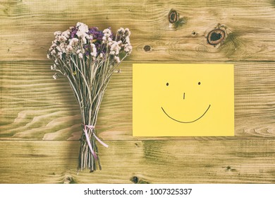 Beautiful bouquet of flowers and smiley face on wooden table.Image is intentionally toned.