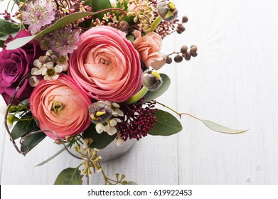 Beautiful bouquet of flowers in tin mug on light background. Closeup, floral composition
