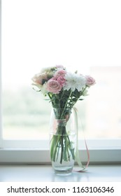Beautiful bouquet of flowers in transparentglass vase on a window