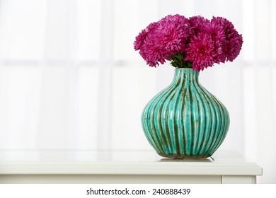 Beautiful bouquet of flowers in vase on window background